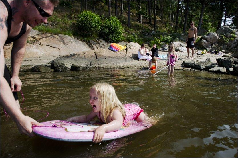 STRANDHYGGE: Kaya (4) prøver å holde seg på badebrettet, mens pappa Jan Erik Bråten jobber for det motsatte. Søsteren Hailey (3) leter etter krabber. Foto: OLE-MARTIN GRAV