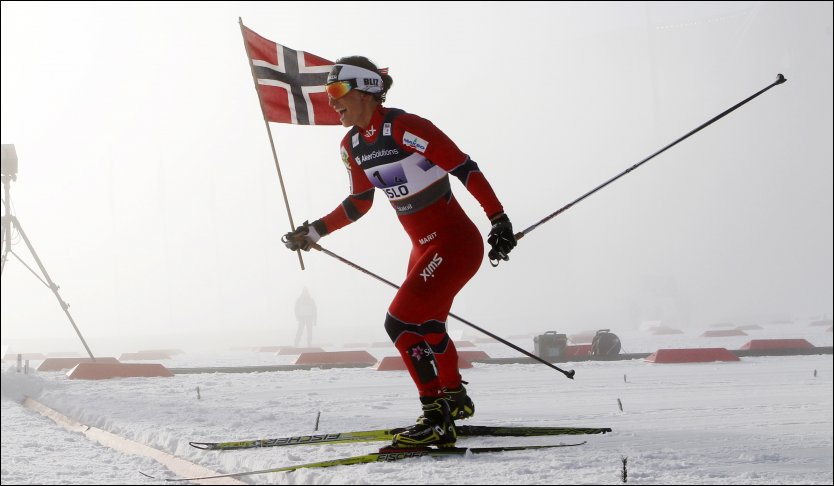 SUKSESSFERD: Marit Bjørgen hentet flagget og krysset mållinjen med det. Foto: Scanpix