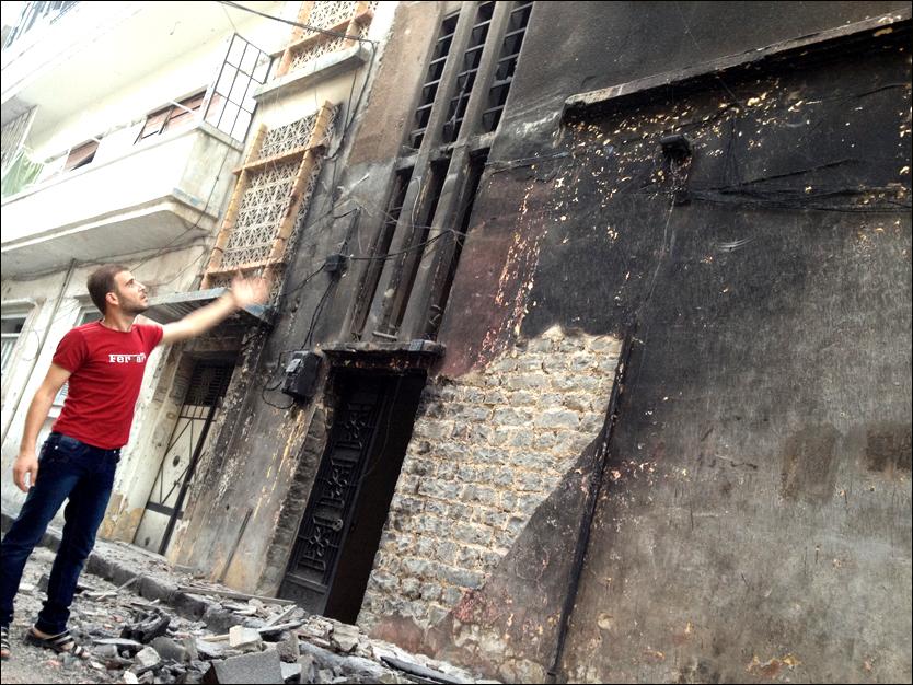 Opprørstalsmannen Abu al-Zayn al-Homsi viser frem en ødelagt bygning. Bildet som skal være tatt fredag viser ødeleggelsene i nabolaget Bab al-Darib i Homs i Syria. Foto: Privat