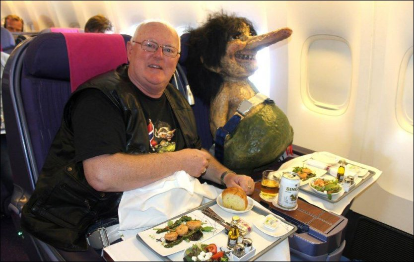 TO BLIDE KARER: Godt fastepent i sidesetet til dansegalla-arrangør Edgar Skjønhals fløy det velvoksne trollet på business-class fra Oslo til Bangkok. Den tause, men blide passasjeren ble raskt et yndet fotomotiv om bord på Thai-flyet. Foto: Privat