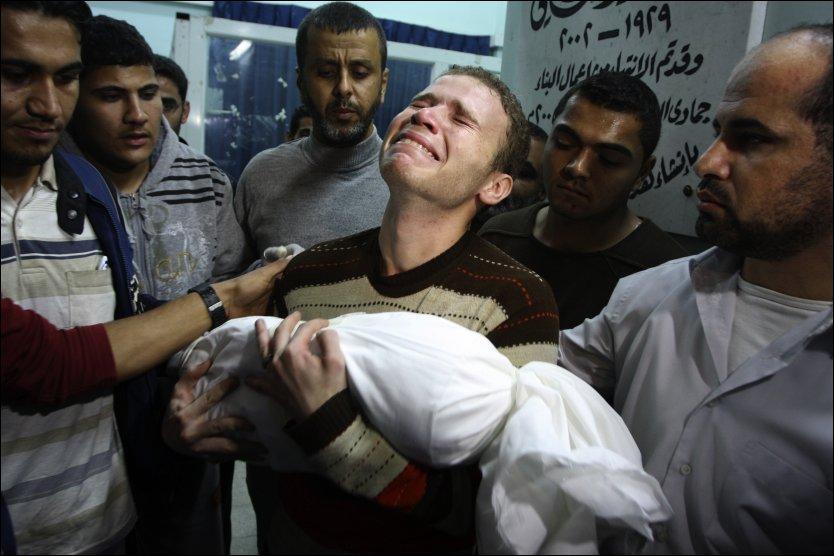 KNUST: Jihad Masharawi fortviler med sin døde 11 måneder gamle sønn i armene. Foto: Majed Hamdan/AP